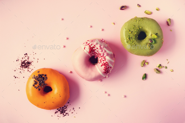 Colorful donuts with icing on pastel pink background. Sweet orange, green, pink doughnuts with - Stock Photo - Images