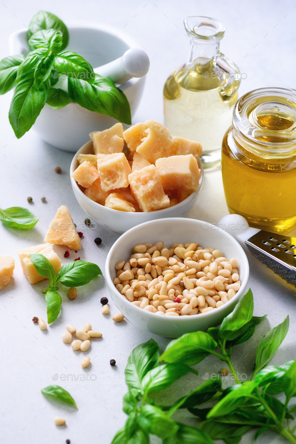 Ingredients for homemade pesto - basil, lemon, parmesan, pine nuts, garlic, olive oil and salt on - Stock Photo - Images