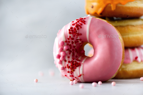 Stack of glazed colorful assorted donuts with sprinkles on grey cement background. Copy space. Sweet - Stock Photo - Images