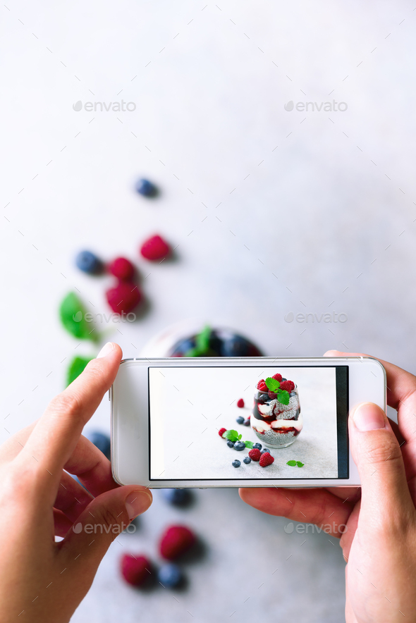 Girl is taking photos of breakfast, chia pudding with berries to mobile phone. Social media concept - Stock Photo - Images