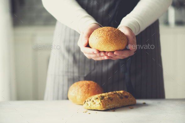 Woman hands holding freshly baked bread. Bun, cookie, bakery concept, homemade food, healthy eating - Stock Photo - Images