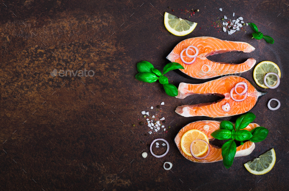 Raw fresh salmon steak with vegetables. Ingredients for cooking on brown background. Space for text - Stock Photo - Images