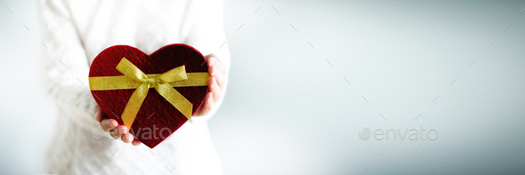 Female hands holding gift box heart shape on grey background. Copy space. Love concept. Banner - Stock Photo - Images