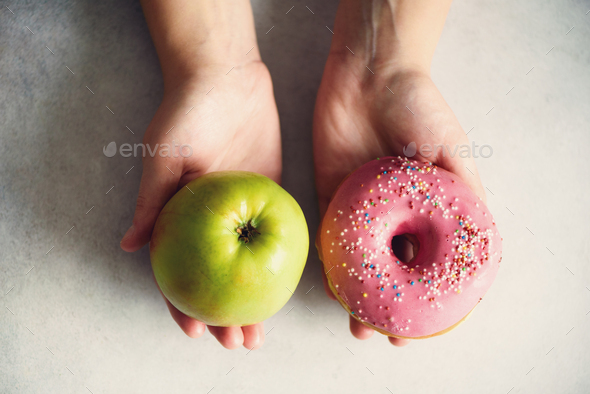 Young woman in white T-shirt choosing between green apple or junk food, donut. Healthy clean detox - Stock Photo - Images