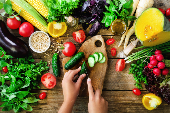 Woman hands cutting vegetables on wooden background. Vegetables cooking ingredients, top view, copy - Stock Photo - Images