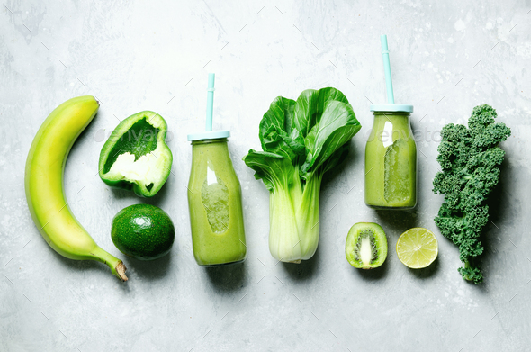 Green smoothie in glass jar with fresh organic green vegetables and fruits on grey background - Stock Photo - Images
