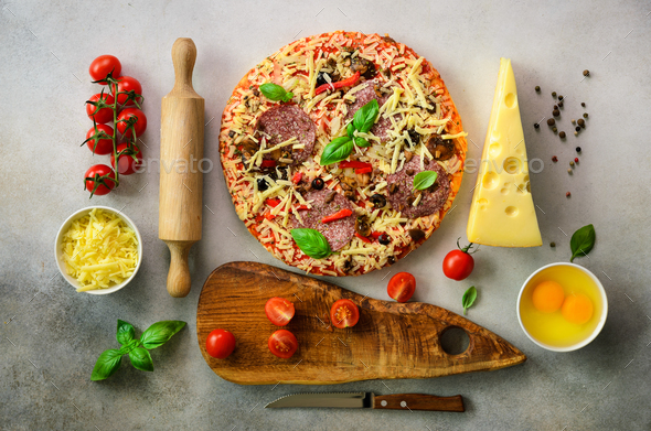 Food ingredients for italian pizza, cherry tomatoes, flour, cheese, basil, rolling pin, board, knife - Stock Photo - Images