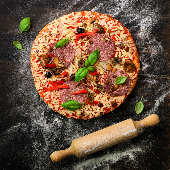 Girl hands making, decopating, preparing pizza with basil leaves on dark background. Top view, copy - Stock Photo - Images