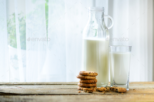 Chocolate chip cookies, bottle and glass of milk on wooden table near window, white background - Stock Photo - Images