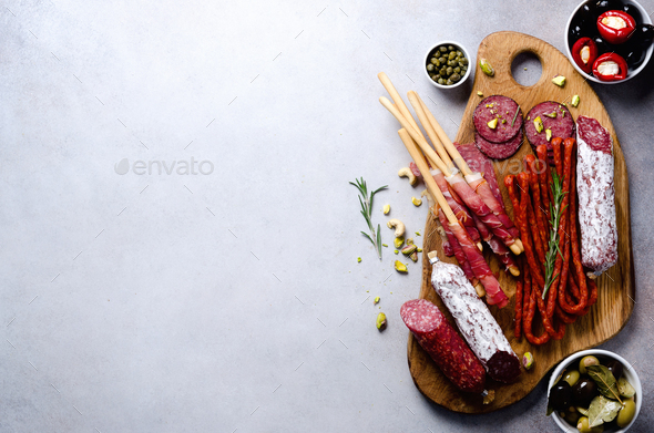 Antipasto plate with meat, olives, grissini bread sticks on grey concrete background. Top view, copy - Stock Photo - Images