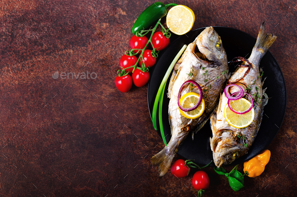 Cooked baked grilled fish, dorado, sea bream with lemon, herbs, vegetables and spices on rustic - Stock Photo - Images