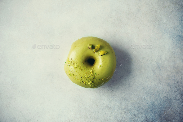 Sweet doughnut with green glaze and pistachio on grey background. Tasty donut on pastel concrete - Stock Photo - Images