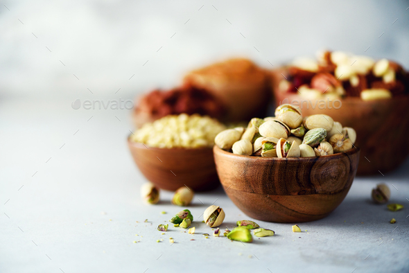 Pistachios nuts in wooden bowl. Food mix background, top view, copy space, banner. Assortment of - Stock Photo - Images