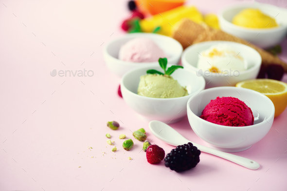 Red, purple, yellow, green, white ice cream balls in bowls, waffle cones, berries, orange, mango - Stock Photo - Images