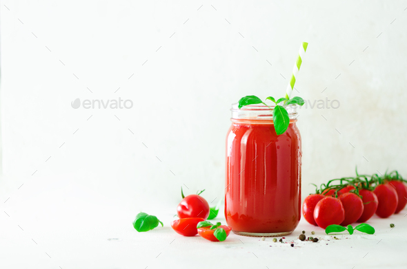 Organic fresh tomato juice in a glass jar, basil, cherry, salt, pepper and straw on light background - Stock Photo - Images