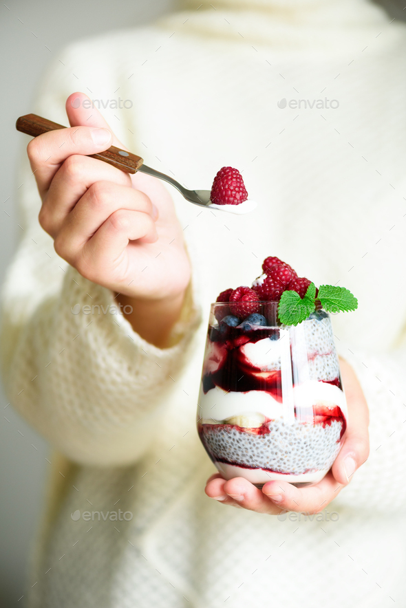 Girl in white sweater holds glass with chia milk dessert, raspberries, blueberries, mint. Healthy - Stock Photo - Images