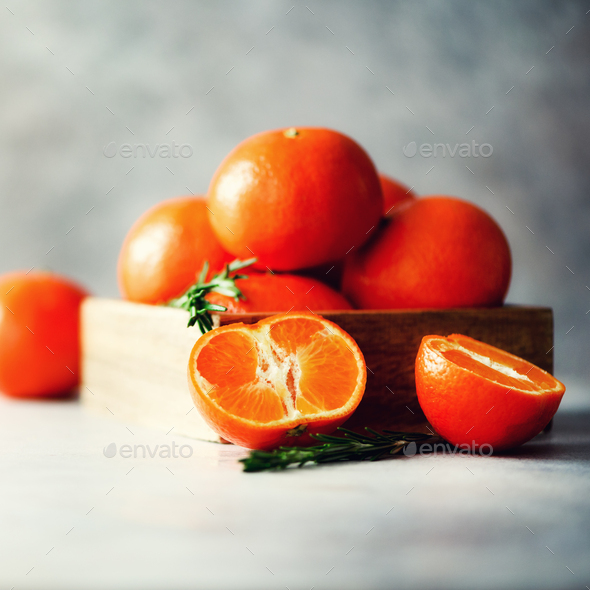 Orange tangerines, mandarins, clementines, citrus fruits with rosemary in wooden box on grey - Stock Photo - Images