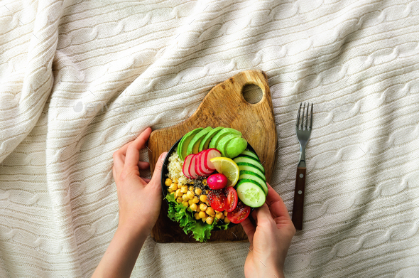 Girl in white jeans holds in hands fork, vegan breakfast meal in bowl with avocado, quinoa, cucumber - Stock Photo - Images