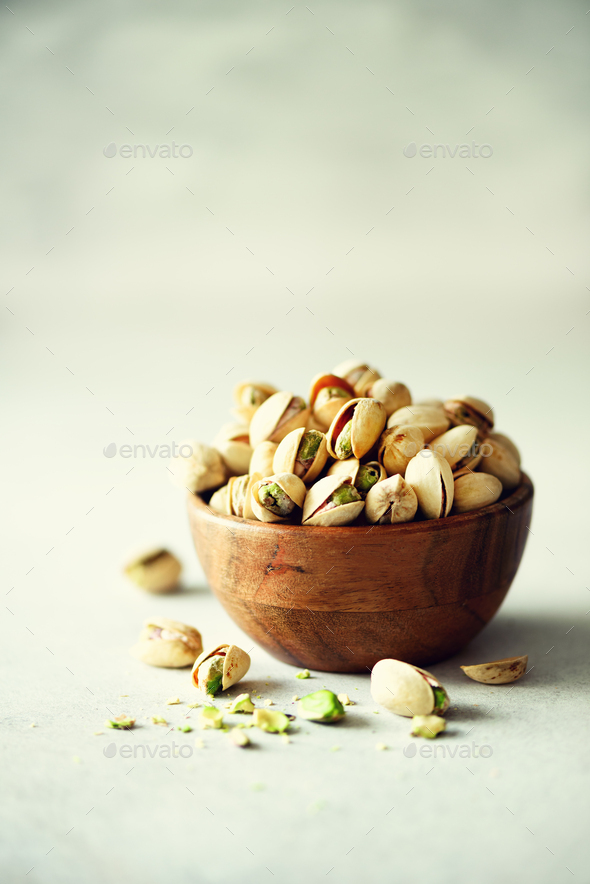 Green salted pistachios in wooden bowls on light concrete background. Copy space for your text - Stock Photo - Images