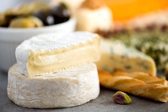 Assortment of hard, semi-soft and soft cheeses with olives, grissini bread sticks, capers, grape, on - Stock Photo - Images