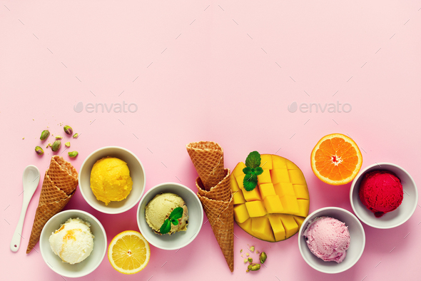 Top view red, purple, yellow, green, white ice cream balls in bowls, waffle cones, berries, orange - Stock Photo - Images