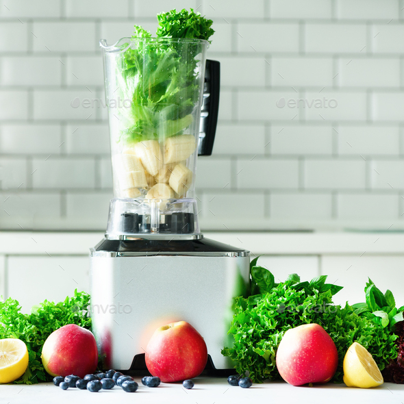 Woman blending lettuce leaves, spinach, aplles, berries, bananas. Homemade healthy green smoothie - Stock Photo - Images