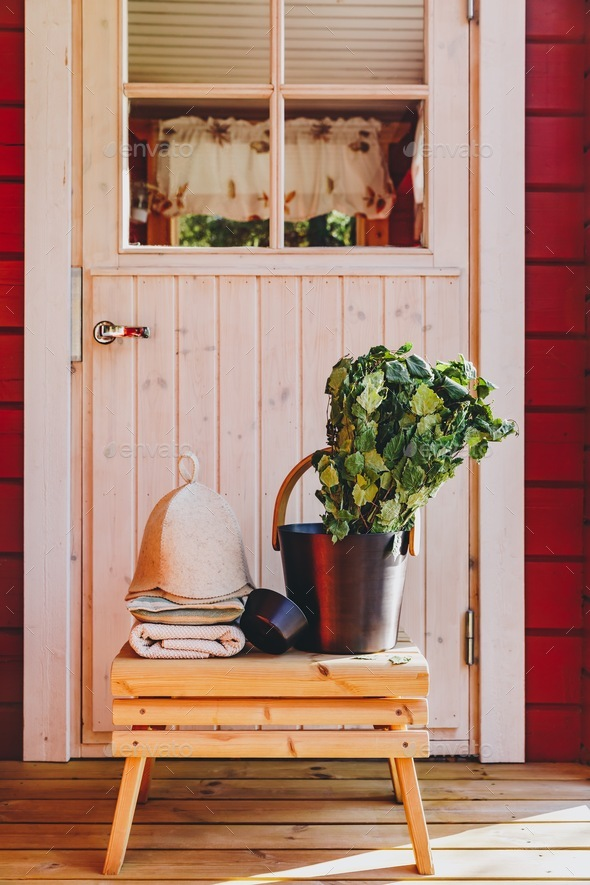 Sauna accessories with birch broom, hat and towels near a red wooden sauna in Finland - Stock Photo - Images