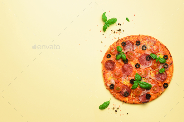 Delicious italian pizza, basil leaves, salt, pepper on yellow background with copyspace. Top view - Stock Photo - Images
