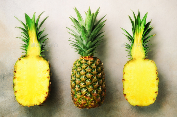 Half slice of fresh pineapple and whole fruit on gray background. Top View. Copy Space. Bright - Stock Photo - Images