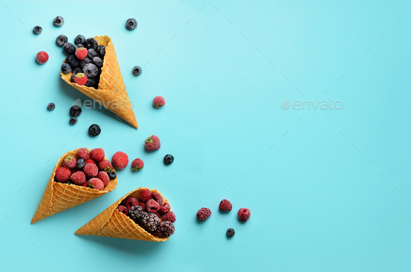 Frozen berries - strawberry, blueberry, blackberry, raspberry in waffle cones on blue background - Stock Photo - Images