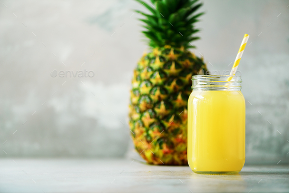 Glass jar of pineapple smoothie and whole fruit on gray background. Copy space. Summer, holiday - Stock Photo - Images