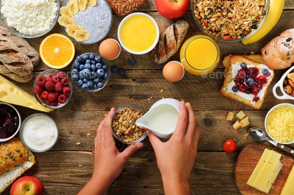 Girl cooking breakfast - granola with yogurt, fruits, berries, milk, yogurt, juice, cheese. Top view - Stock Photo - Images