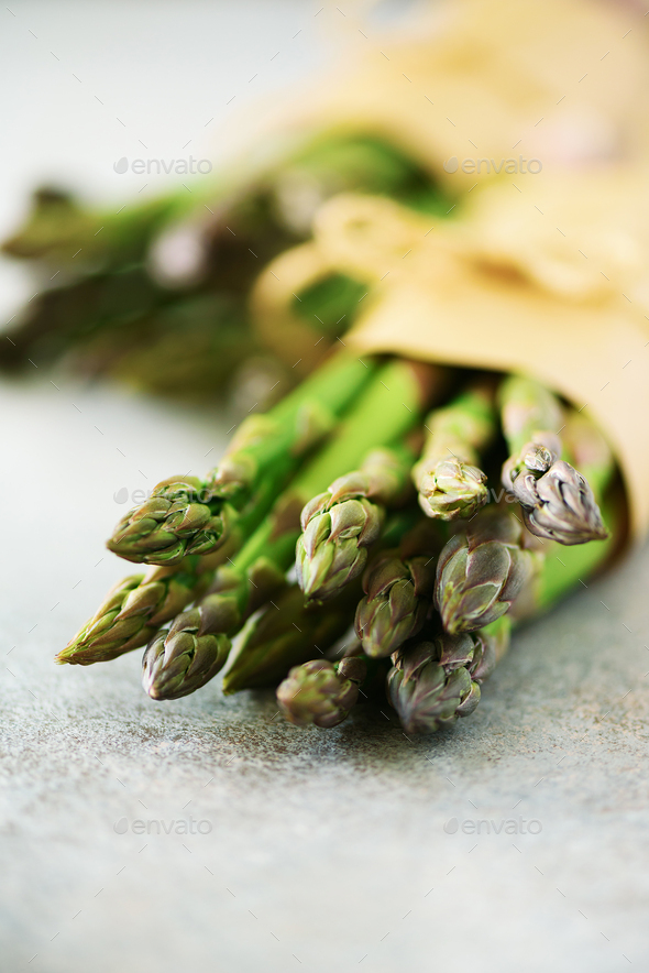 Bunch of fresh asparagus on gray backgrouns. Asparagus on craft paper with packthread. Raw, vegan - Stock Photo - Images