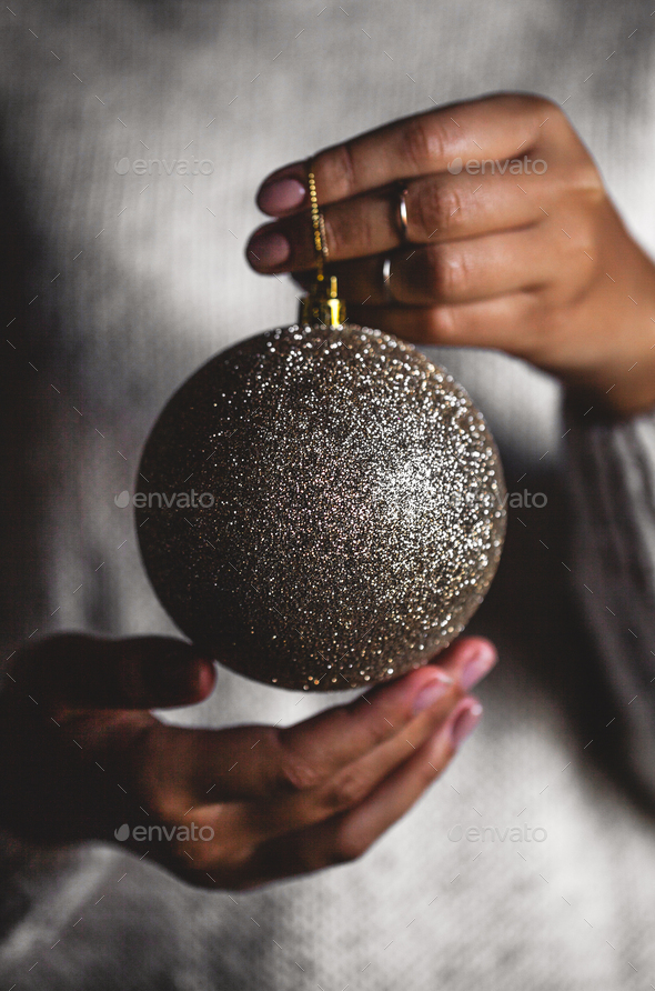 Woman in warm sweater holding toy glass decorative ball in hands, copy space. Christmas, new year - Stock Photo - Images