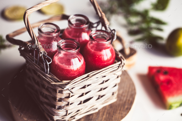 Watermelon juice in jars with a basket with mint leaves and lime citrus - Stock Photo - Images