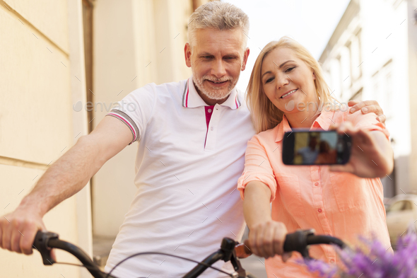 Loving mature couple taking selfie with bike - Stock Photo - Images
