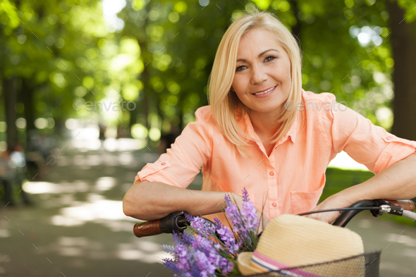 Portrait of beautiful woman with bike in summer day - Stock Photo - Images