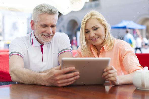 Smiling mature couple enjoying the wireless internet - Stock Photo - Images