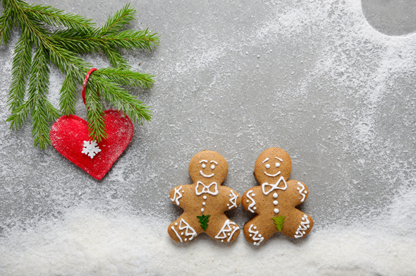Flat lay at two gingerbread men having a walk on snow under fir - Stock Photo - Images