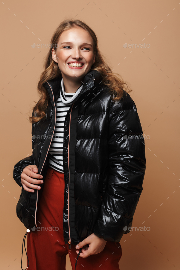 Young cheerful woman with wavy hair in black down jacket happily looking aside over beige background - Stock Photo - Images