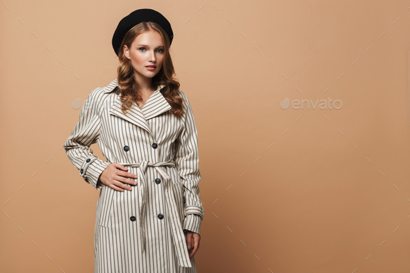 Attractive woman in striped coat and black hat thoughtfully looking in camera over beige background - Stock Photo - Images