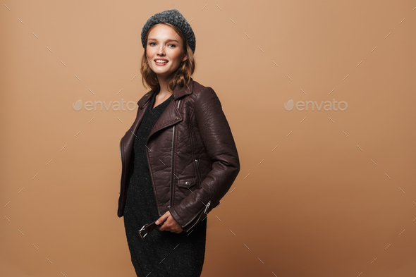 Young pretty smiling woman in hat, leather jacket and black dress dreamily looking in camera - Stock Photo - Images