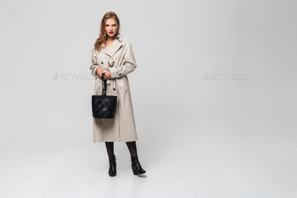 Young attractive serious woman with wavy hair in striped coat holding black bag. Full length - Stock Photo - Images