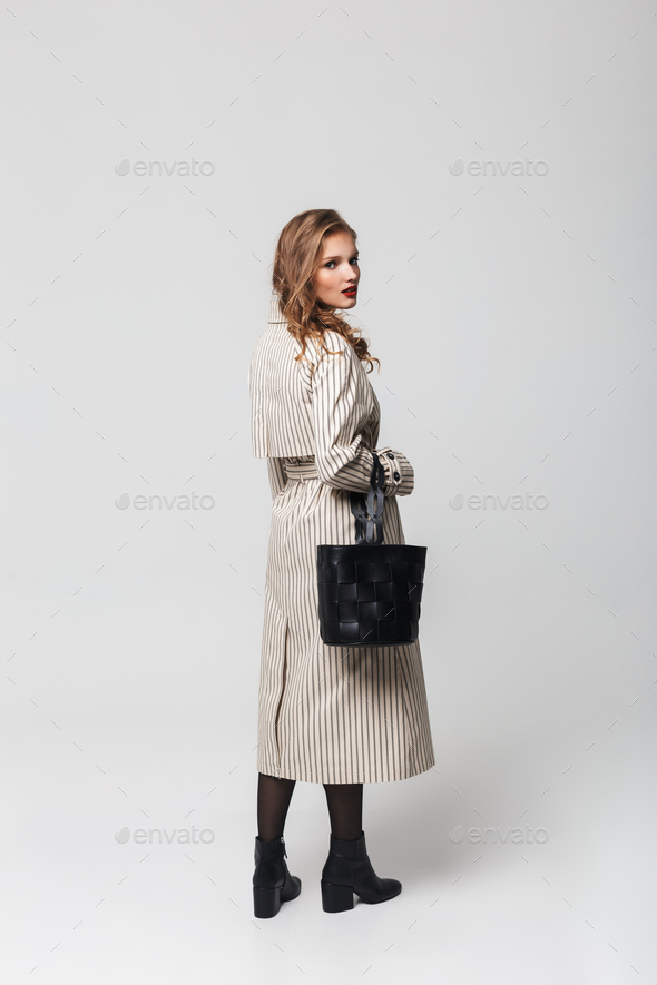 Young attractive woman with wavy hair in striped coat holding black bag dreamily looking in camera - Stock Photo - Images