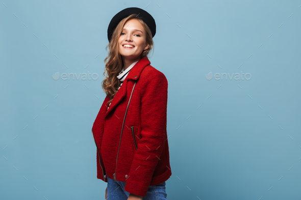 Young pretty smiling woman with wavy hair in black beret and red jacket happily looking in camera - Stock Photo - Images