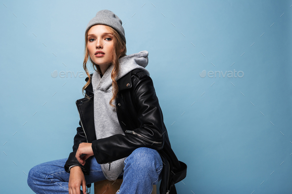 Young beautiful woman with wavy hair in gray hat and black leather jacket dreamily looking in camera - Stock Photo - Images