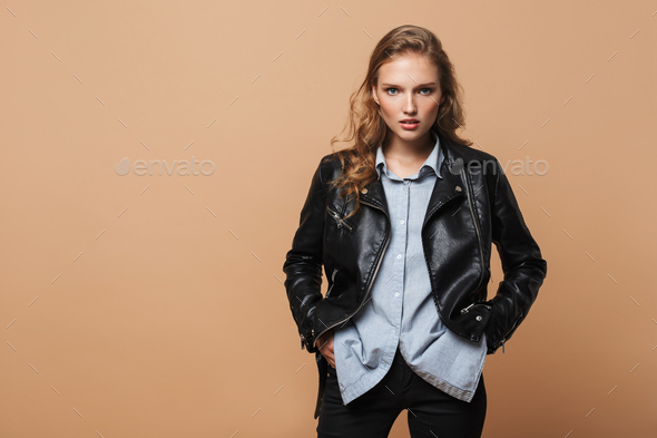Beautiful girl with wavy hair in black leather jacket and shirt holding hands in pockets - Stock Photo - Images