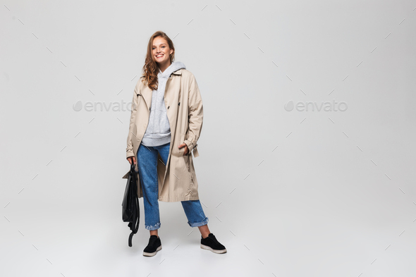 Young smiling woman in trench coat and jeans holding black backpack happily looking in camera - Stock Photo - Images