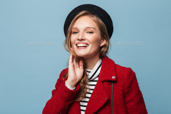 Young beautiful smiling woman with wavy hair in beret and red jacket joyfully looking in camera - Stock Photo - Images