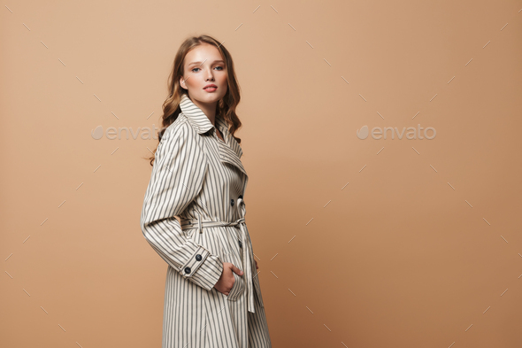 Young beautiful woman with wavy hair in coat thoughtfully looking in camera over beige background - Stock Photo - Images